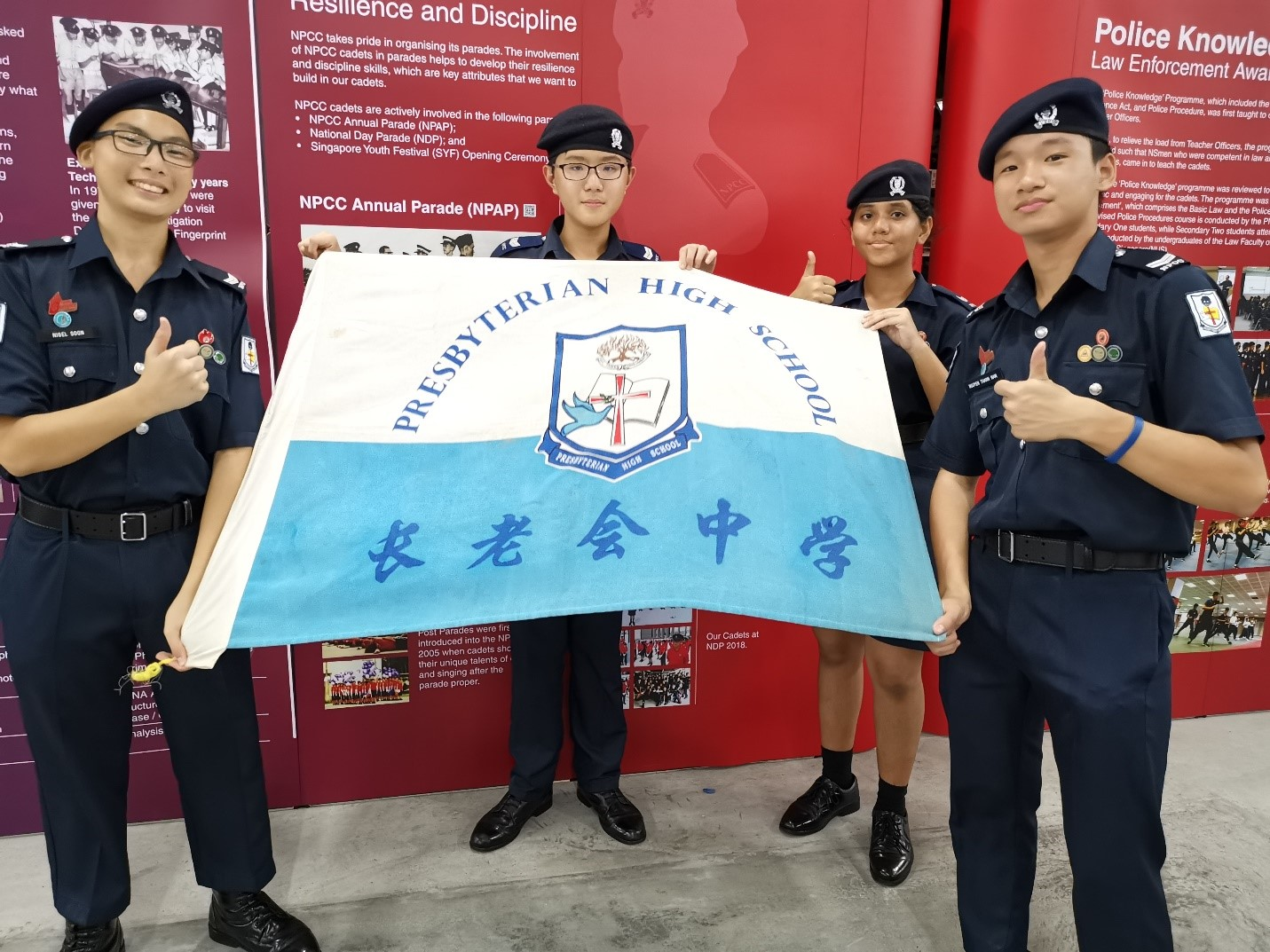 School Cadet Representatives at NPCC Annual Parade holding school flag high.jpg